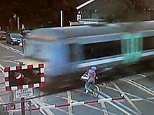 На ВИДЕО: велосипедистка выехала на  ж/д переезд за секунду до поезда